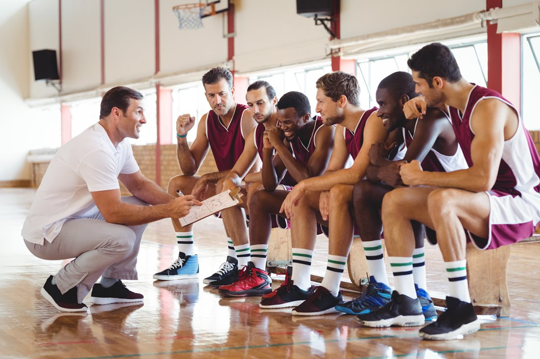Basketball coach talking to team sat on a bench