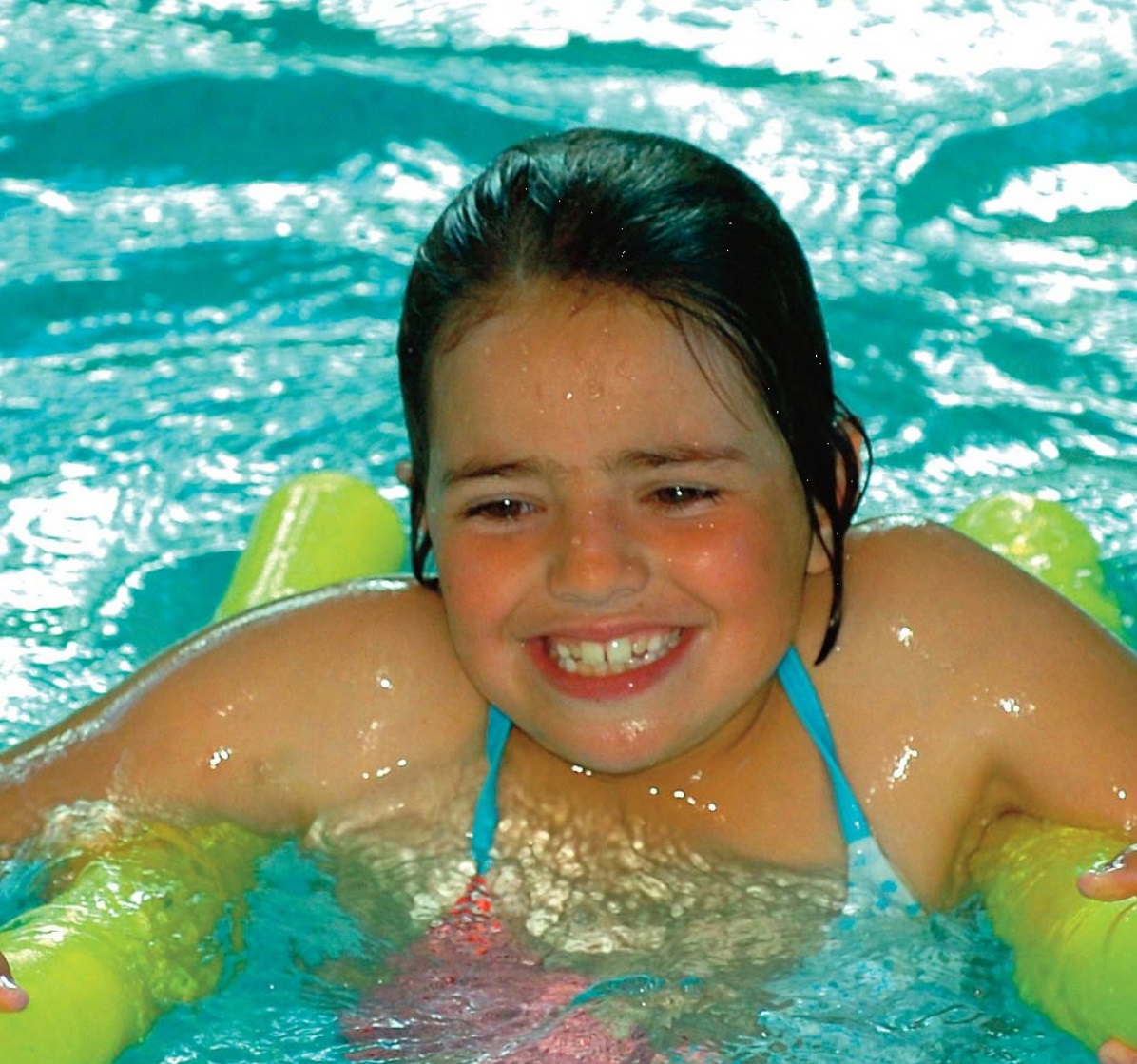 A child has fun in the swimming pool using a bright yellow float