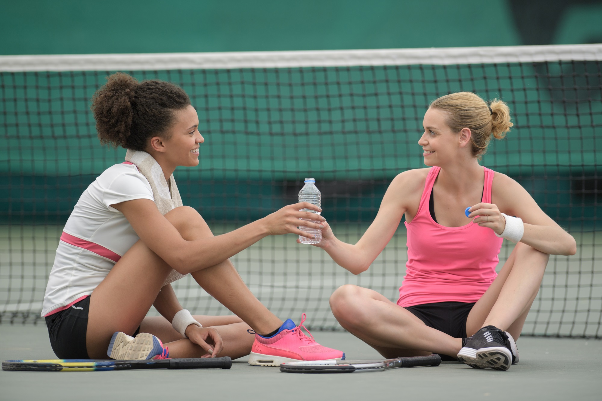 Women sharing a bottle of water on the tennis court