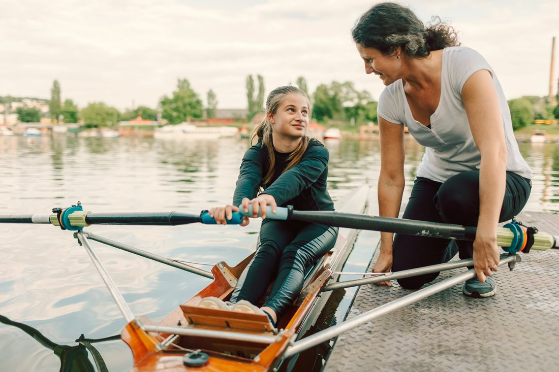 Young rower in discussion with her coach