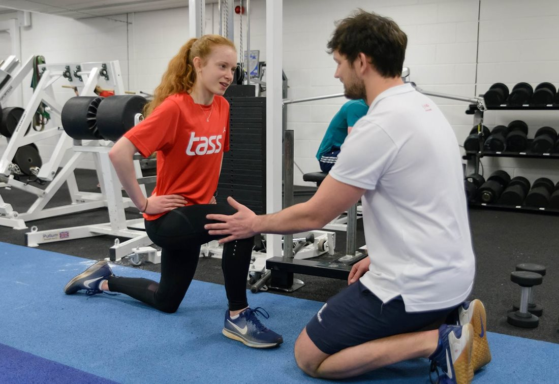 Young TASS athlete with coach in gym