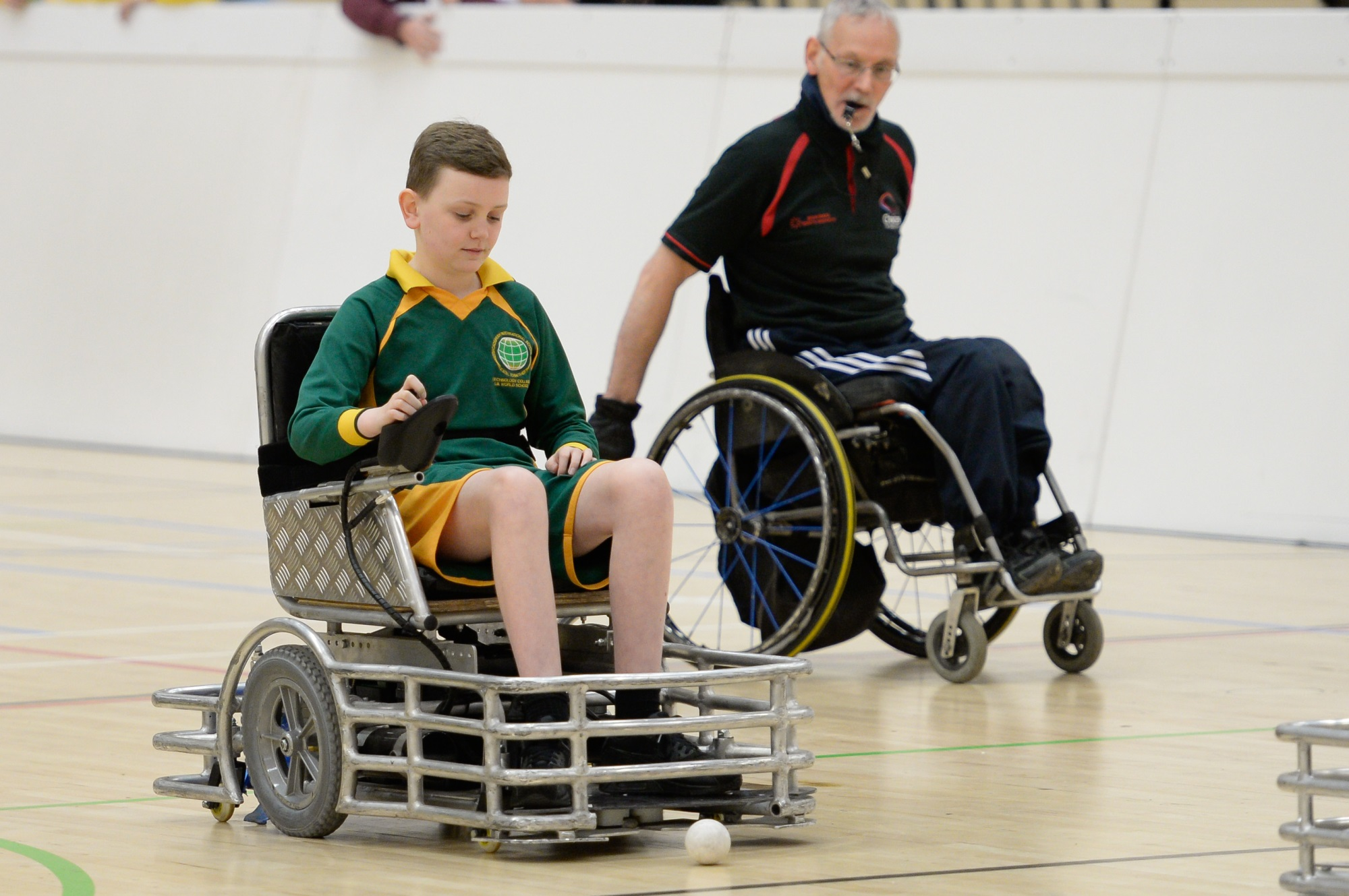 A child enjoys some ball games in their wheelchair in a sports hall