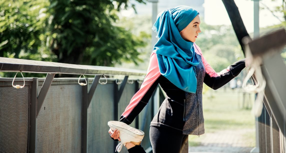 Young Muslim woman in a hijab and exercise clothes, pausing to stretch during a run