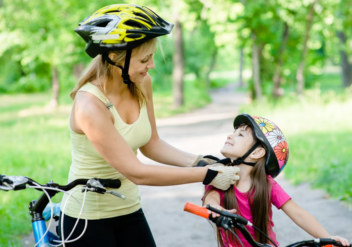 Mum wearing cycling helmet and gloves helps daughter to put on cycling helmet