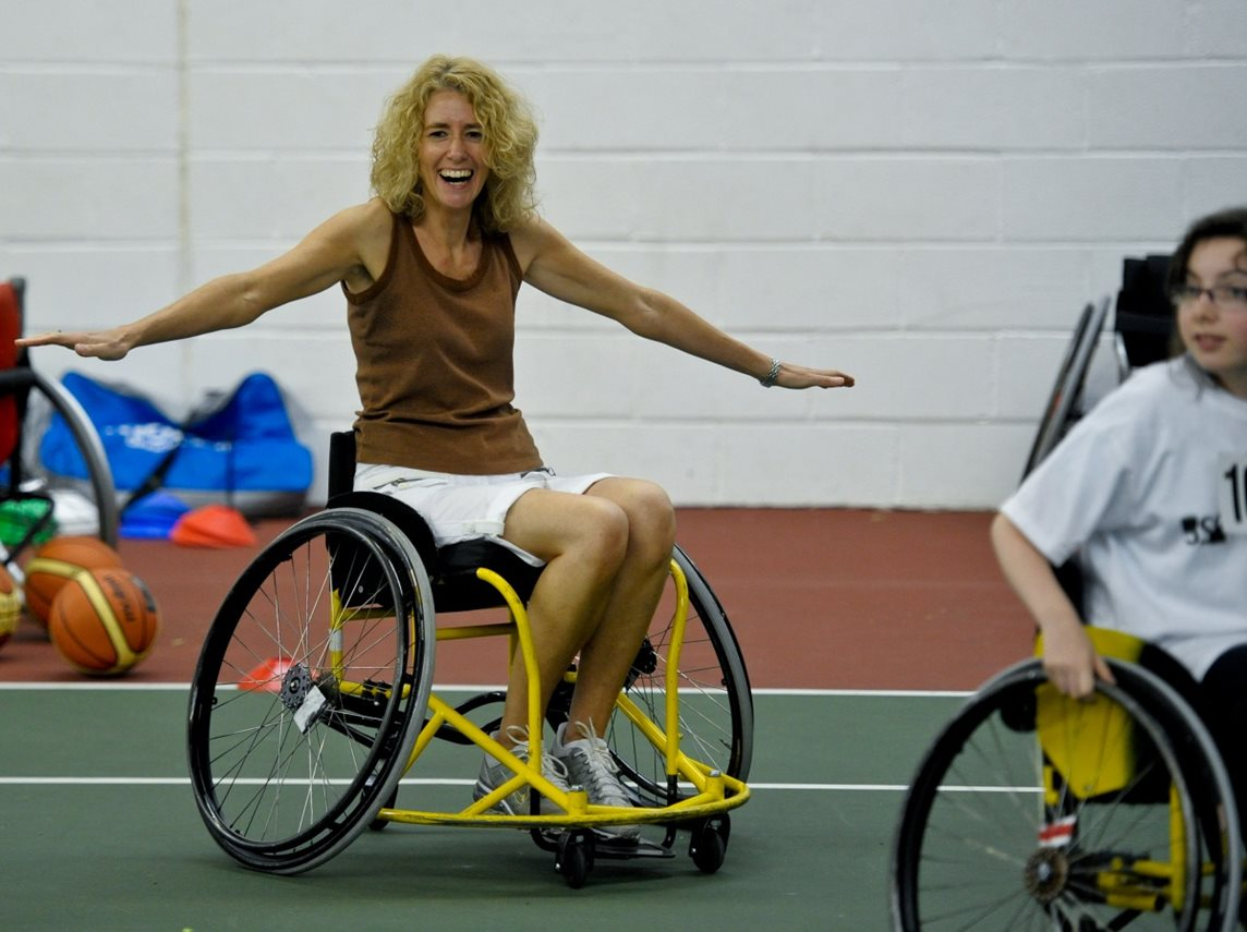 A wheelchair user smiles and stretches out her arms during an on-court training session