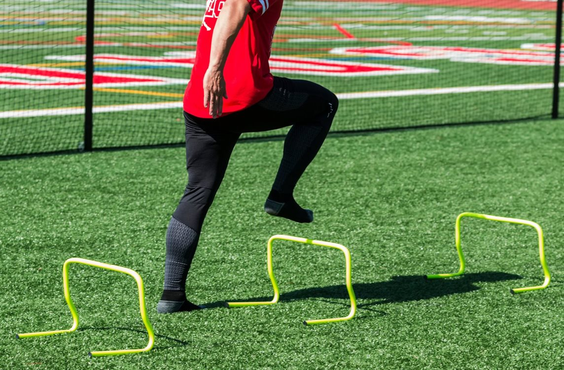 Young athlete developing footwork skills with mini-hurdles